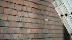 Inserting a brush in a borehole in a cavity wall Stock Footage