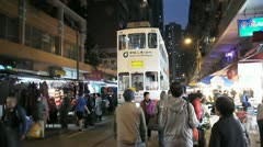 Hong Kong tram moving across night market Stock Footage