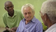 Group of old black and caucasian men talking in park Stock Footage