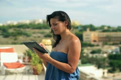 Happy woman with tablet computer on the terrace Stock Footage