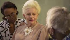 Group of elderly black and caucasian women talking in park Stock Footage