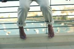 Portrait of sad man sitting on the balustrade of on the terrace, crane shot Stock Footage