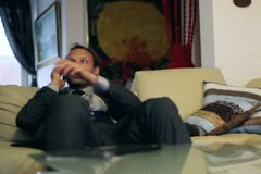 Businessman gets coffee from wife during a telephone call in livingroom Stock Footage