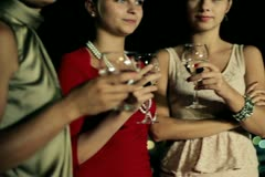 Three female friends enjoying night party on the terrace, crane shot - stock footage