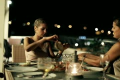 Female friends celebrating dinner on the terrace at night, steadycam shot Stock Footage