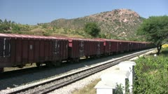 A Freight train is passing by a rural station in India Stock Footage
