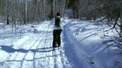 A woman cross country skiis in the mountains Stock Footage