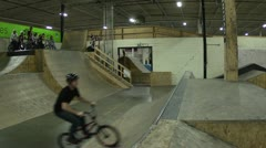 BMXer does tricks in an indoor skatepark Stock Footage