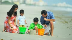 Hispanic family spending summer holiday playing on sandy beach Stock Footage