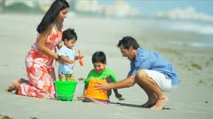 Latin American boys building sand castles with parents on beach  - stock footage