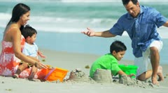 Latin American boys building sand castles with parents on beach  Stock Footage