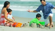 Stock Video Footage of Latin American boys building sand castles with parents on beach