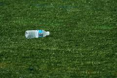empty water bottle on grass - stock photo