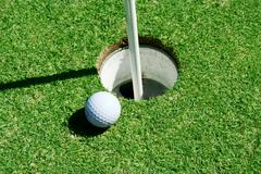 golf ball on green near hole - stock photo