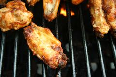 Chicken wings cooking on the grill Stock Photos