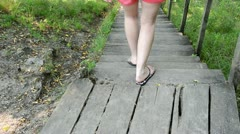 Woman in red shorts climb down wooden stairs in park Stock Footage