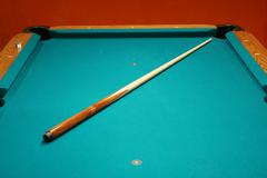 cue stick on a pool table - stock photo