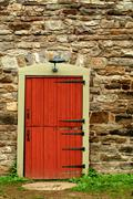 red door on a old stone building - stock photo