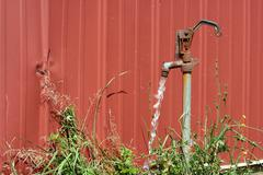 old water spigot with running water - stock photo