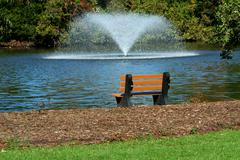 Fountain on a pond with park bench Stock Photos