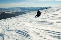 Knapsack and tripod in winter mountains Stock Photos