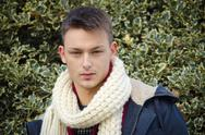 Attractive young man with scarf. holly bush behind Stock Photos