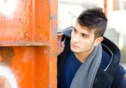 Attractive young man looking beyond metal structure Stock Photos