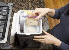 packing lunch into carry bag - stock photo