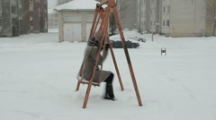 Woman coat sit old retro steel swing winterstorm snow fall Stock Footage