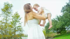 Caucasian female parent playing with little child in park Stock Footage