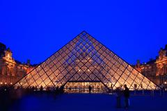 paris - april 16: entrance of louvre pyramid shines at dusk during the summer - stock photo