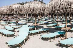 Loungers under palm tree leaves umbrellas on the beach Stock Photos