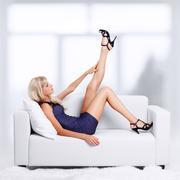 Blond girl on sofa Stock Photos