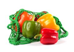 Fresh  sweet peppers in a green string bag Stock Photos