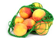 the peaches in a green string bag - stock photo