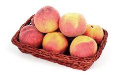 Peaches in basket Stock Photos