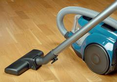 Vacuum cleaner on a oak parquet Stock Photos