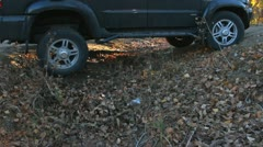 SUV drives through a ditch in the woods Stock Footage