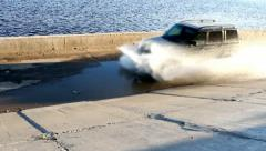 SUV drives through a puddle at speed Stock Footage