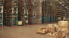 Fork Lift Moving Merchandise Between Huge Shelves In A Warehouse - stock footage