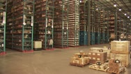 Stock Video Footage of Fork Lift Moving Merchandise Between Huge Shelves In A Warehouse