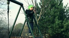 Little boy standing on ladder in autumn playground and waving Stock Footage