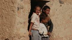 Moroccan children waving near mud building Stock Footage