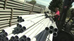 Workers Moving and Stacking Bundles of Tubing Stock Footage