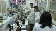 View of Laboratory Work Table with Many Containers As Three Workers Talk Stock Footage