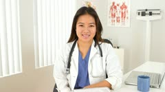 Portrait of female Asian doctor sitting at desk Stock Footage