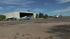 Prop Plane Taxiing Runway With Hanger in the Background Stock Footage