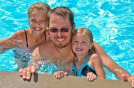 Dad and daughters in pool Stock Photos