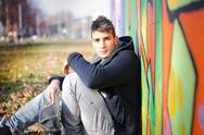 Handsome young man sitting on ground against colorful graffiti Stock Photos