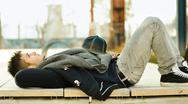 Attractive young man laying on bench Stock Photos